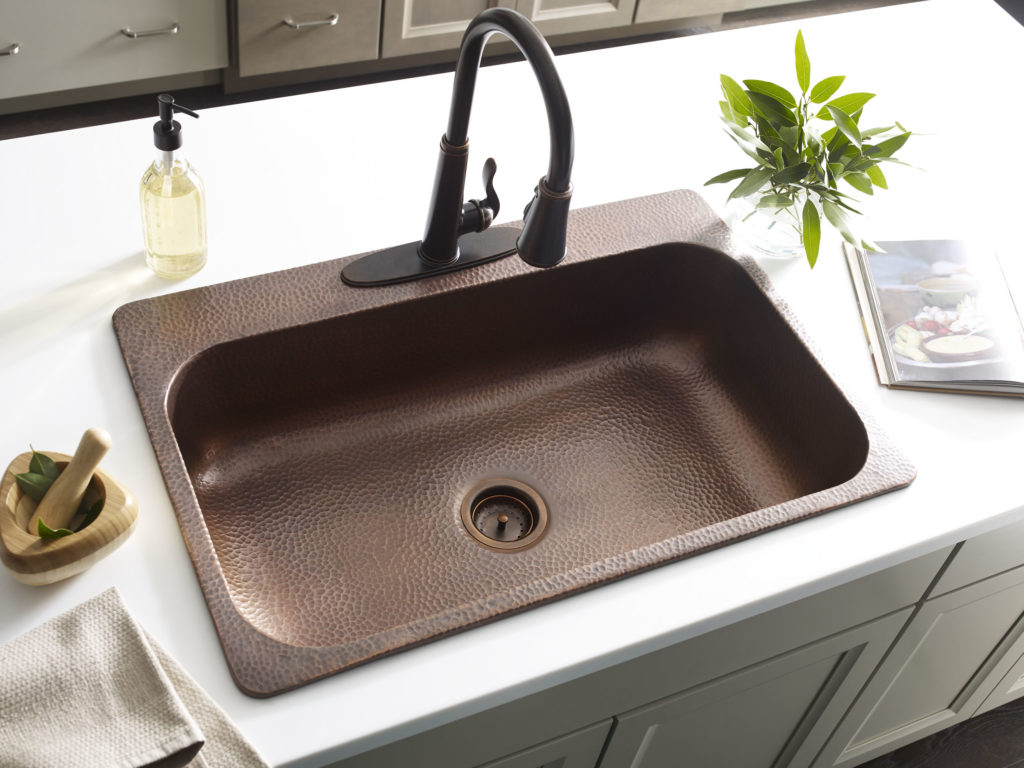 installed angelico copper drop-in sink with white countertop and rustic bronze pfister faucet