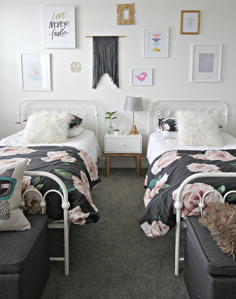 girl's bedroom with 2 beds, white walls, floral bedspreads