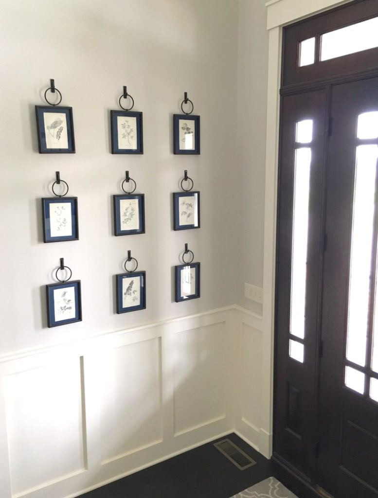 white walled foyer with picture frames and wood framed door