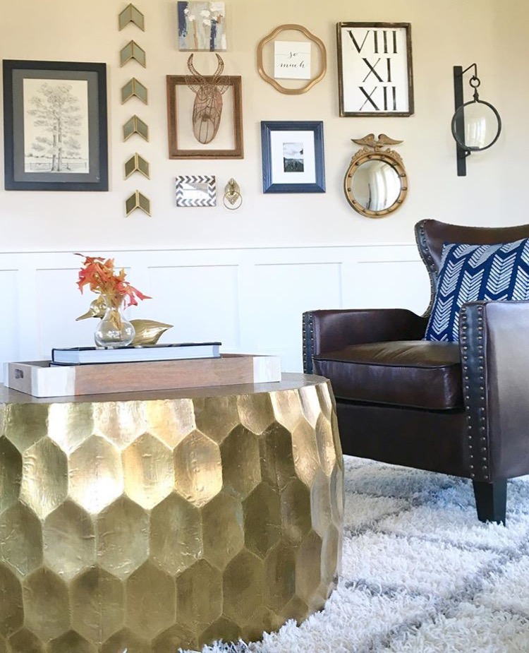white walled living space with leather chair and metallic table
