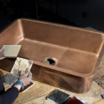 woman matching countertop samples to orwell undermount copper sink on wooden table