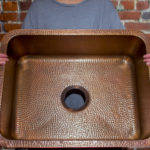 person showing inside of renoir undermount hand hammered 16-gauge copper kitchen sink