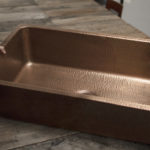 david undermount copper kitchen sink sitting on a rough wooden table
