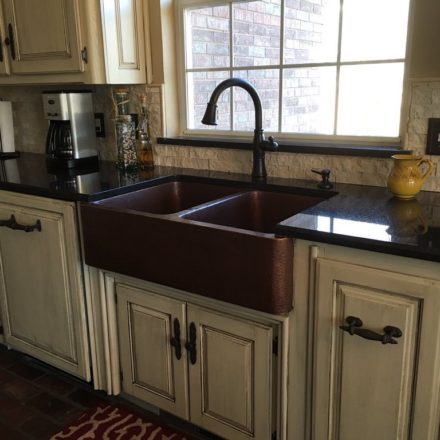 double-bowl copper apron front sink in a kitchen