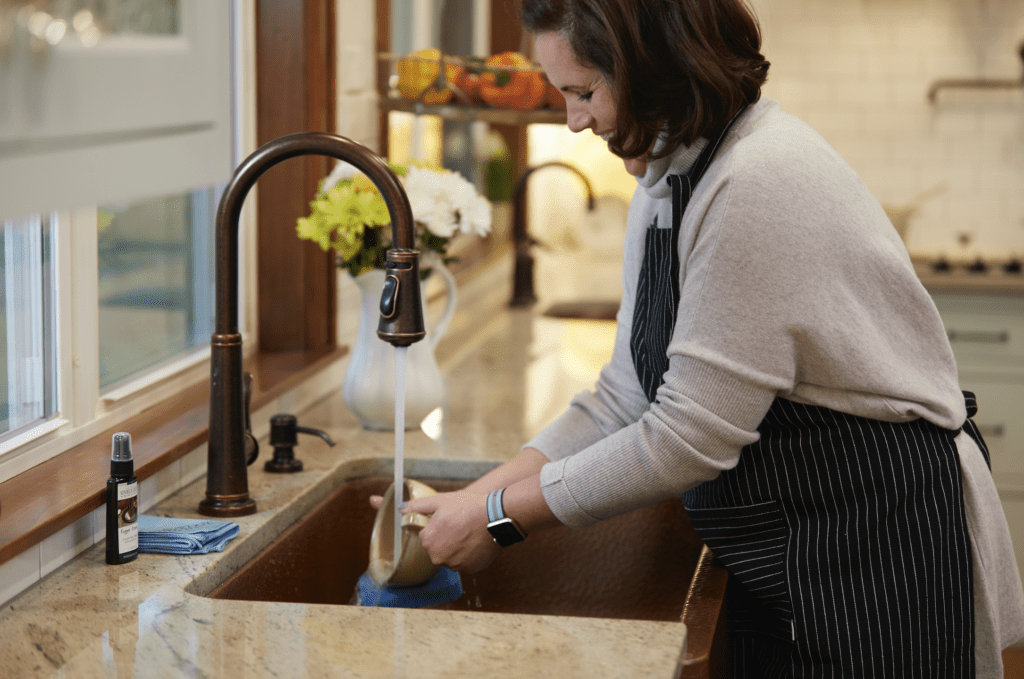 woman washing hands at copper sink
