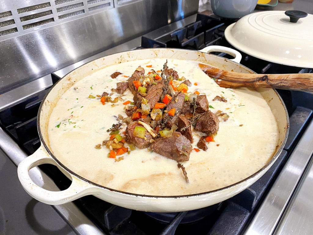 adding veggies and meat to liquid
