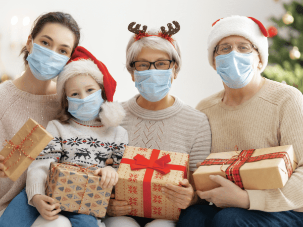 Family wearing masks while holding gifts